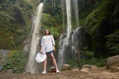 Sekumpul-Wasserfall mit einem beuatiful touristischen Mädchen in Bali, Indonesien lizenzfreie stockbilder