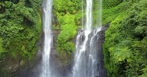 Sekumpul Waterfall in Bali with tourists, Indonesia . Drone aerial Shot stock footage
