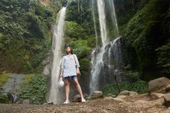 Sekumpul waterfall with a beuatiful tourist girl in Bali, Indonesia royalty free stock images
