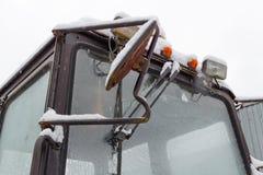 Sekundärscheinwerfer des alten Traktors mit der orange warnenden Lampennahaufnahme bedeckt mit Schnee Stockfoto
