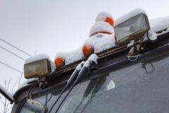Sekundärscheinwerfer des alten Traktors mit der orange warnenden Lampennahaufnahme bedeckt mit Schnee Stockbild