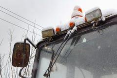 Sekundärscheinwerfer des alten Traktors mit der orange warnenden Lampennahaufnahme bedeckt mit Schnee Stockbilder