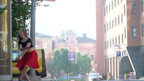 Sekwencja jako dziewczyna w czerwonym czerń wierzchołku i spódnicie skacze w tanu, filmuje w miasto letnim dniu swobodny ruch zbiory wideo
