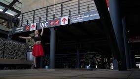 Sekwencja osamotniona blondynka z długie włosy w czerwonej spódnicie angażuje w ulicznych tanach po środku centrum handlowego zbiory wideo