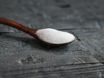 Sel blanc, finement moulu dispersé sur une table foncée en bois avec une cuillère Photographie stock