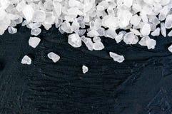 Sel brut de mer sur le fond noir de pierre d'ardoise, plan rapproché, l'espace libre pour votre texte Images libres de droits