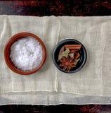 sel de mer, anis d'étoile, feuille de laurier, cardamome noir et bâton de cannelle disposés dans des deux petites cuvettes placé  image stock