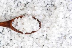 Sel de mer dans la cuillère en bois sur le fond en bois, plan rapproché, l'espace libre pour votre texte Photographie stock libre de droits
