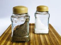 Sel et poivre dans un support en verre de dispositif trembleur et de dispositif trembleur de poivre sur une planche à découper images stock
