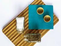 Sel et poivre dans un support en verre de dispositif trembleur et de dispositif trembleur de poivre sur une planche à découper photographie stock libre de droits