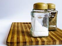 Sel et poivre dans un support en verre de dispositif trembleur et de dispositif trembleur de poivre sur une planche à découper photos stock