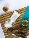 Sel et poivre dispersés des dispositifs trembleurs de sel en verre et des dispositifs trembleurs de poivre sur une planche à déco photos stock