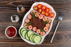 Sel et poivre, ketchup, plat divisé avec les morceaux frits de saucisses, riz rouge, concombres, tomate, fourchette sur la table  photo libre de droits