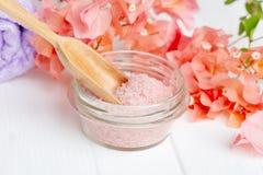 Sel rose de l'Himalaya de station thermale dans un bol en verre avec la fleur de bouganvillée sur un fond blanc Massage, aromathe photographie stock