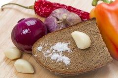 Sel sur le pain et des légumes de seigle Images libres de droits