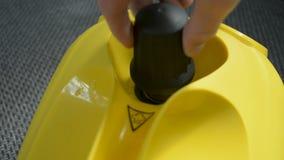 A selagem de fechamento molha o tampão no dispositivo do líquido de limpeza do vapor com o close up da mão do sinal de aviso filme