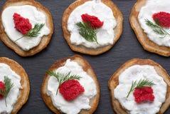 Selbst gemachte Blinis mit Sauerrahm und rotem Kaviar Stockfotos
