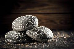 Selbst gemachte Brötchen für schwarze Burger auf dunklem Steinhintergrund Selektiver Fokus stockfotos