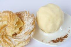 Selbst gemachte Butter auf einer weißen Porzellanplatte, Vanillepuddingkuchenring mit Puderzucker, Mandeln, zerrieb Zimt, lizenzfreies stockbild