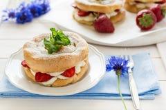 Selbst gemachte Chouxgebäckringe mit Hüttenkäsecreme und -erdbeeren verzierten tadellose Blätter Stockbild