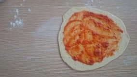 Selbst gemachte dünne Krustenpizza mit Pizzasoße auf die Oberseite vor backen Stockfotografie