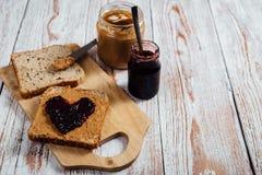 Selbst gemachte Erdnussbutter und Geleesandwich auf hölzernem Hintergrund lizenzfreie stockfotografie
