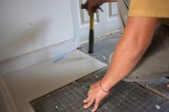 Selbst gemachte ersetzende Boden Keramikfliesen heraus gebrochen und ein Heftpflaster der Fliese das alte, um Kleber zu zementier lizenzfreies stockfoto