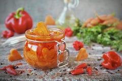 Selbst gemachte in Essig eingelegte Karotten mit Knoblauch und Paprika in den Glasgefäßen stockbild