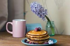 Selbst gemachte flaumige Pfannkuchen mit frischen Beeren auf einer blauen Platte auf einem Holztisch stockbilder