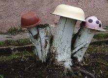 Selbst gemachte Gartenskulptur - Pilzwulstling auf dem Gras Der Pilz wird von einer alten Platte und von einem Klotz gemacht Upcy Stockbilder