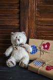Selbst gemachte Geschenke des Valentinstags im Kraftpapier mit Herzen etikettiert, Spielzeugbär Stockfotografie