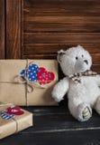 Selbst gemachte Geschenke des Valentinstags im Kraftpapier mit Herzen etikettiert, Spielzeugbär Lizenzfreies Stockfoto