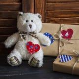 Selbst gemachte Geschenke des Valentinstags im Kraftpapier mit Herzen etikettiert, Spielzeugbär Stockfotos