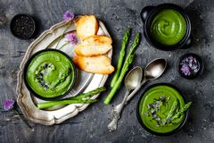 Selbst gemachte grüne Frühlingsspargelcremesuppe verziert mit schwarzen Samen des indischen Sesams und essbaren Schnittlauchblume stockfotos