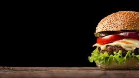 Selbst gemachte Hamburgernahaufnahme mit Rindfleisch, Tomate, Kopfsalat, Käse und Zwiebel auf Holztisch Fastfood auf dunklem Hint stockfotografie