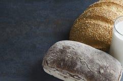 Selbst gemachte köstliche Brotlaibe, Glas Milch Geschmackvolle Imbisszeit Rustikale Stimmung Kopieren Sie Raum für Text lizenzfreies stockfoto