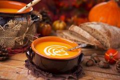 Selbst gemachte Kürbissuppe auf einer rustikalen Tabelle mit Herbstdekorationen Lizenzfreies Stockfoto