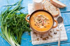 Selbst gemachte Kürbissuppe mit Sahne, Brot, Grüns und Kürbiskerne auf einem hölzernen Hintergrund Spitzen-viev lizenzfreie stockfotos