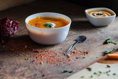 Selbst gemachte Kürbissuppe mit Sahne und Petersilie auf einem hölzernen Hintergrund Stockbild