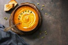 Selbst gemachte K?rbissuppe in einer Lehmplatte gedient mit Sahne, Samen und dunkelbraunem rustikalem Hintergrund des Toasts Drau stockfoto