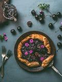Selbst gemachte Kirschtorte auf hölzerner Platte und rustikaler Küchentischhintergrund mit Stau und Tischbesteck Lizenzfreies Stockfoto