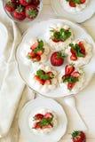 Selbst gemachte kleine Erdbeere-pavlova Meringe backt mit mascarpone Creme und frischen tadellosen Blättern zusammen Stockfoto