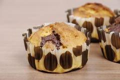 Selbst gemachte kleine Kuchen mit Schokolade auf einem Holztisch lizenzfreie stockfotos