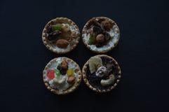 Selbst gemachte Kuchen, gebackene Oberteile, Weißkäse, Nüsse und Süßigkeits-Frucht auf einer schwarzen Tabelle Stockbilder