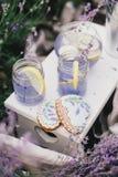 Selbst gemachte Lavendellimonade mit frischen Zitronen auf einem weißen hölzernen Behälter lizenzfreie stockfotografie