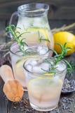 Selbst gemachte Limonade mit Lavendel, frischen Zitronen und Rosmarin auf dem Holztisch, vertikal lizenzfreie stockbilder