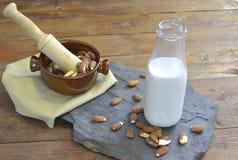 Selbst gemachte Mandelmilch in der Flasche mit Mandeln in einer Schüssel Molkereialternativmilch stockfoto