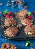 Selbst gemachte Muffins der Schokolade mit rapsberry auf blauem Hintergrund Stockfotografie