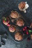 Selbst gemachte Muffins der Schokolade mit rapsberry auf schwarzem Hintergrund Lizenzfreie Stockfotografie