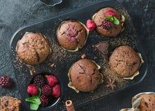 Selbst gemachte Muffins der Schokolade mit rapsberry auf schwarzem Hintergrund Lizenzfreies Stockfoto